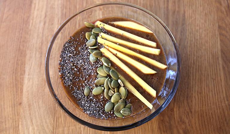 Smoothie i glassbolle, pyntet med mango, gresskar- og chiafrø.