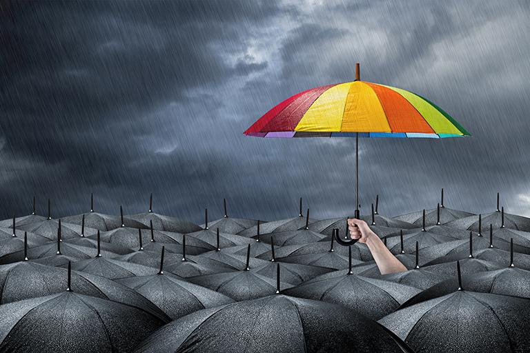 Grå paraplyer og en farget paraply